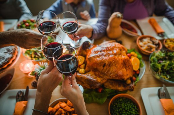 Group of people sitting around a table on Thanksgiving day toasting with glasses of red wine